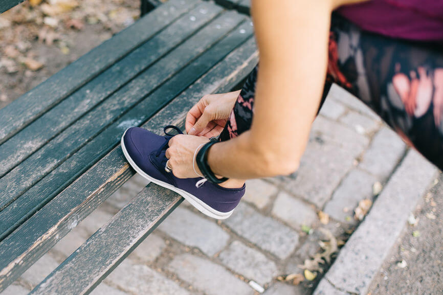 woman tying sneaker on green old bench